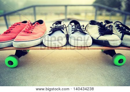 closeup of skateboarding shoes on skateboard at skatepark