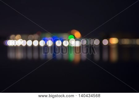 Bokeh Out Of Focus Lights Of Buildings Lit Up For Night Time Reflecting In Water