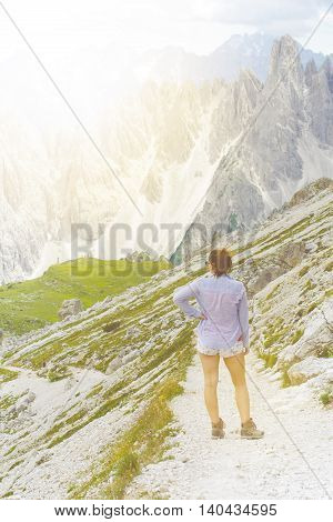 woman hiker have a rest on a mountains Peaks like a background. Sunny day.Trekking. Lens flare. Succesful backpacker enjoy a view