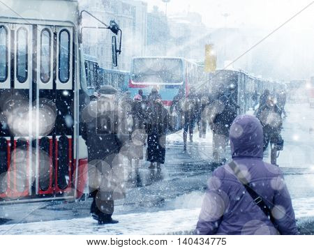 people walking on busy city street during snow
