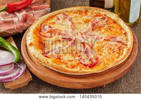 Pizza with bacon, tomatoes, cheese and pepper