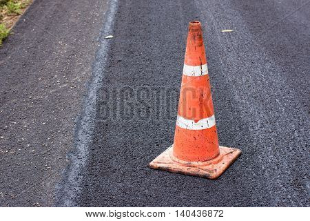 Road construction cones on an asphalt surface.