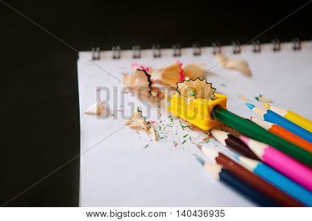 Colored pencils, sharpener and shavings on a notepad on a black background