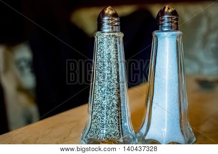 Pepper and salt shakers in closeup view, on a table.
