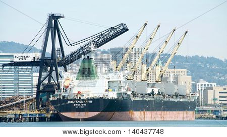 Oakland CA - July 27 2016: Bulk Cargo Ship CHAYANEE NAREE docked at the Schnitzer Steel terminal at the Port of Oakland. Schnitzer Steel recycles scrap metal into finished steel products such as rebar and wire rod.