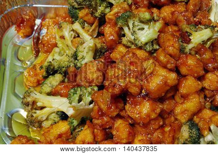 Saucy Chinese crispy chicken and broccoli  close up served in picnic tin