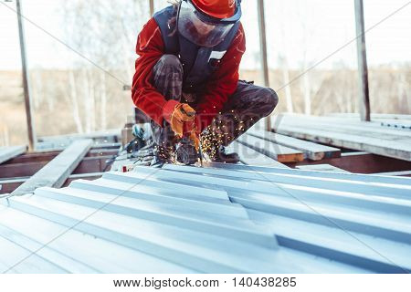 man in helmet sawing iron with sparks