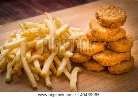 Golden brown Chicken nuggets and French fries on a wood background