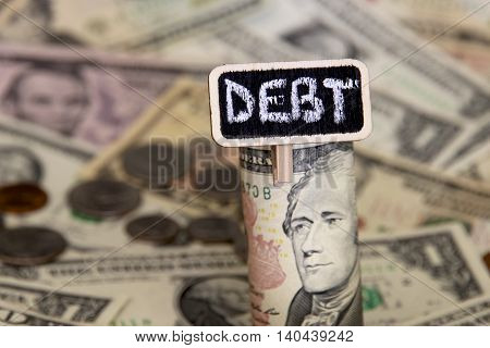 Debt sign with a background of American dollars.