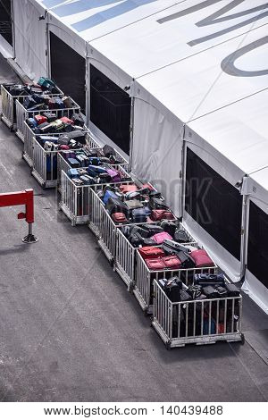 Many bins full of luggage by a tent for a cruise ship