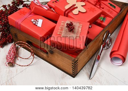 Closeup of a wood box filled with Christmas presents all wrapped in red paper and decorated. On a rustic wood surface with scissors, paper roll and red berries.