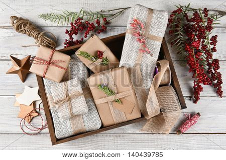 High angle view of a wood box filled with Christmas presents surrounded by wrapping tools and supplies both natural and man made.