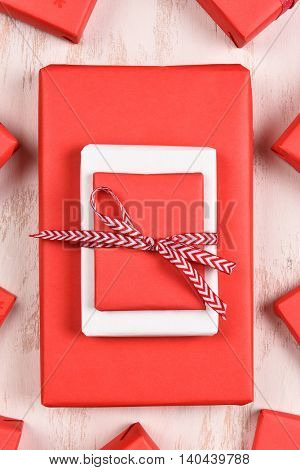 A large Christmas present on a white rustic surface surrounded by smaller gifts. The packages are primarily red.