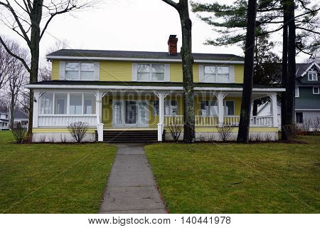 WEQUENTONSING, MICHIGAN / UNITED STATES - DECEMBER 22, 2015: A large yellow home on Beach Drive in Wequetonsing.