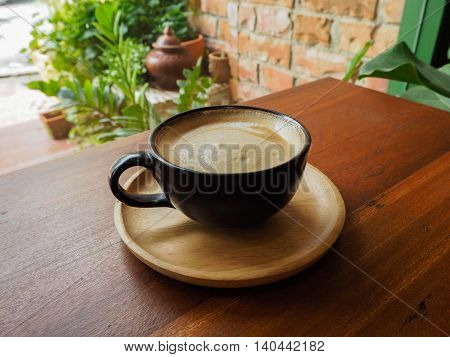 Hot coffee in black cup for asia garden background.