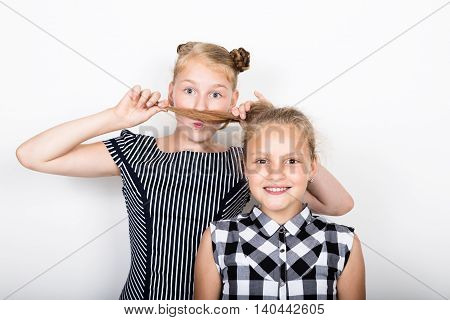 Two cute little girlfriend expressing different emotions. Funny kids. Best friends pamper and posing.