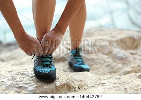 young woman rock climber tying shoelace on stone