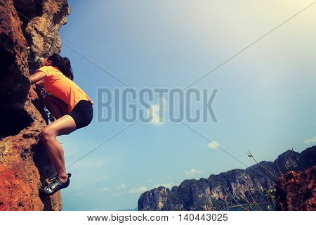 young woman rock climber climbing at seaside mountain rock