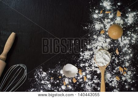 Flour in wooden spoon whisk rolling pin and eggshell on wooden table for baking background