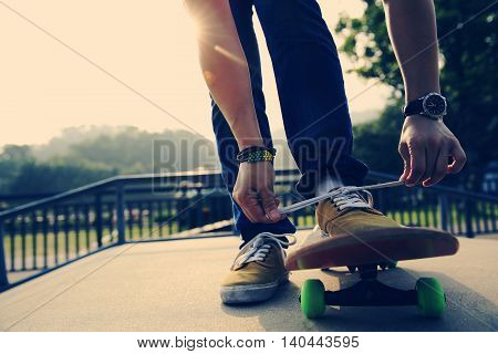 young skateboarder tying shoelace on skatepark ramp