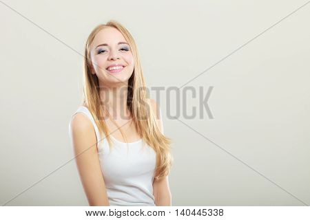 Portrait of young beautiful blonde woman smiling on gray background
