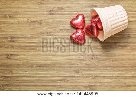 Heart shaped sweets wrapped in a bright red foil lying in a ceramic vase on a wooden texture. Background for romantic themes.