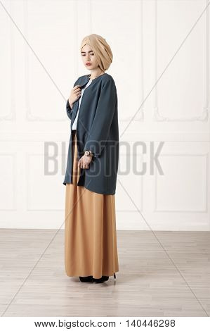Studio photo girl Caucasoid appearance in a closed modern Muslim clothes with a turban on his head on a white background classical
