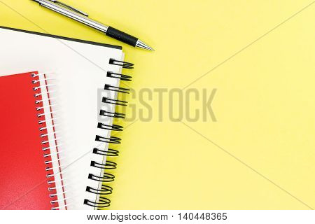 Red And Black Notepad With Open Clean Page And Pen On Yellow Table