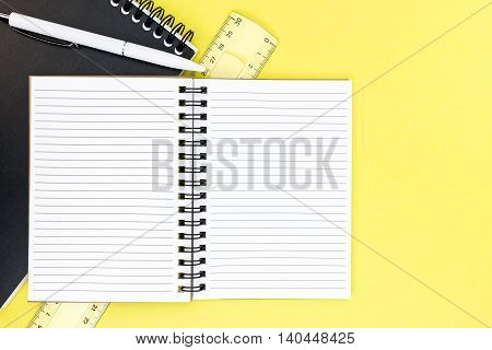 Notepad, Ruler, Ballpoint Pen And Opened Ruled Notebook On Yellow Writing Desk