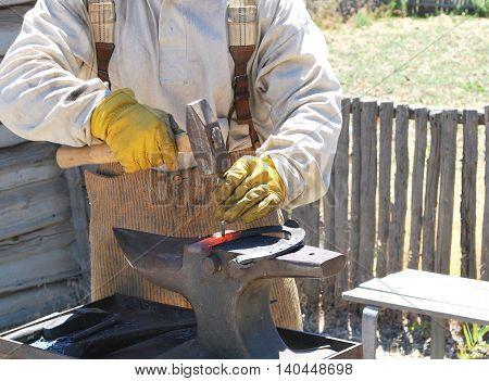 Male farrier working on a horseshoe outside.
