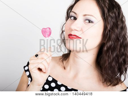 Portrait of happy beautiful young woman licking sweet candy and expressing different emotions. pretty woman with heart shaped lollipop.