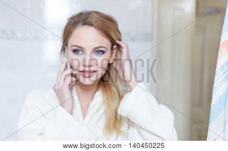 Blonde woman in towel calling from bathroom