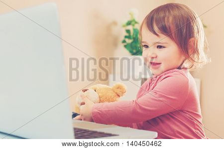 Toddler Girl Using A Laptop With Her Teddy Bear
