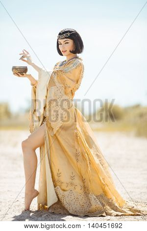 Woman pours potion, poisons water. Fashion Stylish Beauty Portrait Holding and Drinking Cup. Girl standing in golden dress outdoors in desert. Hot sunny weather