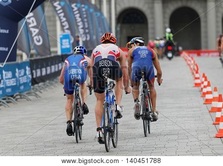 STOCKHOLM SWEDEN - JUL 02 2016: Rear view of a group of male triathlete cyclists Gordon Benson (GBR) Eric Lagerstrom (USA) Velasques (VEN) and competitors in the Men's ITU World Triathlon series event July 02 2016 in Stockholm Sweden