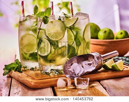 Alcohol mint sprig drink. Wooden boards three glasses with alcohol drink and ice cubes. Drink two hundred ninety-four cocktail mohito and scoop ice with straw. Country life. Outdoor. Light background.