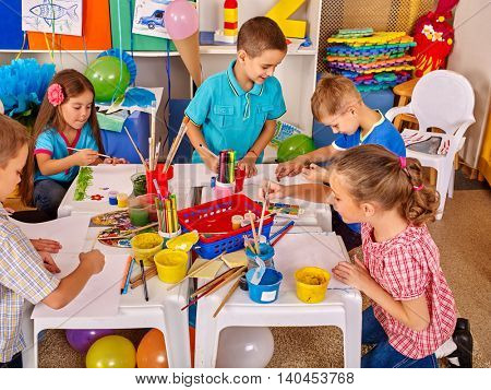 Children without teacher painting on paper at table in primary school. Children learn on their own by paint colors.