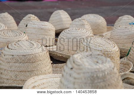 Handmade Panama Hats are stacked for sale at the outdoor craft market