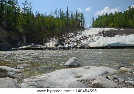 Glacier on the shore of Irkut River in its beginning in the Sayan Mountains in sunny day