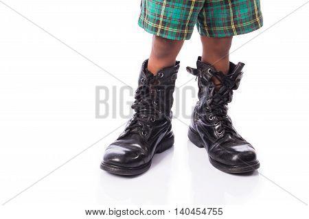 little boy wearing big shoe on white background