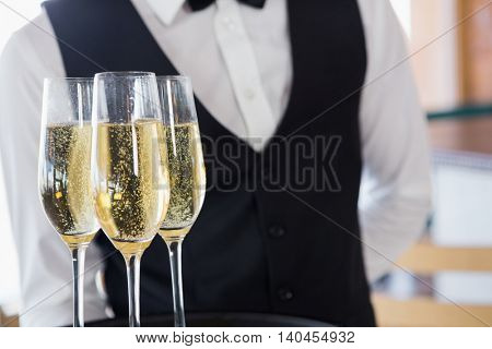 Mid section of waiter holding glasses of champagne in restaurant