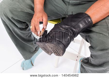 Man cleaning combat shoes on white background