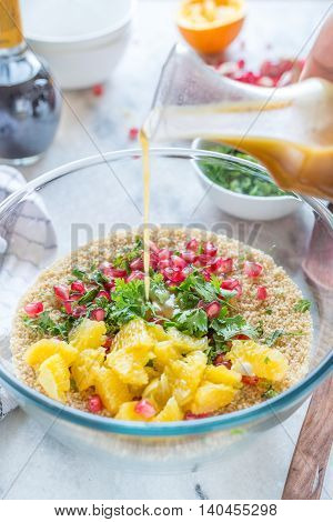 Couscous salad with orange vinaigrette in glass bowl in the kitchen