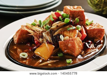 Braised tofu with onion and sauces on white plate