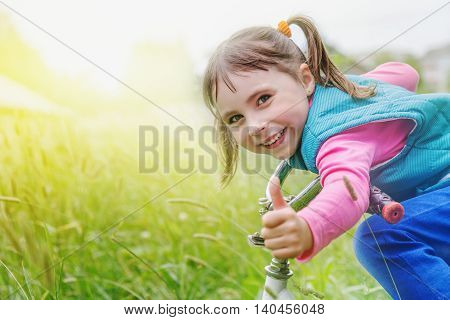 Young girl is cycling into on a green meadow.