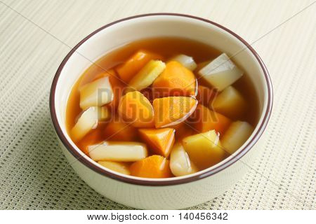 Ginger sweet potato soup in white bowl in restaurant