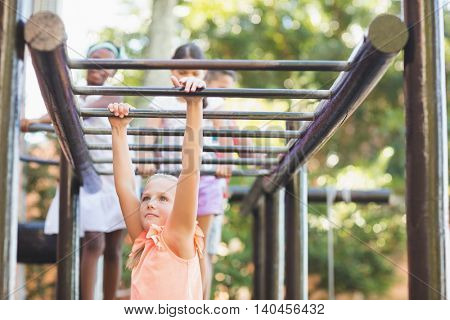 Schoolgirl hanging on monkey rack at playground