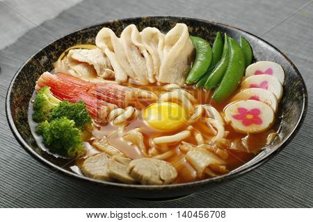 Udon noodle in japanese style with tempura pork fish paste egg and broccoli