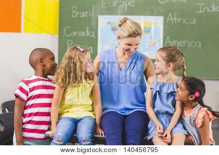 Teacher and kids having fun in classroom at school