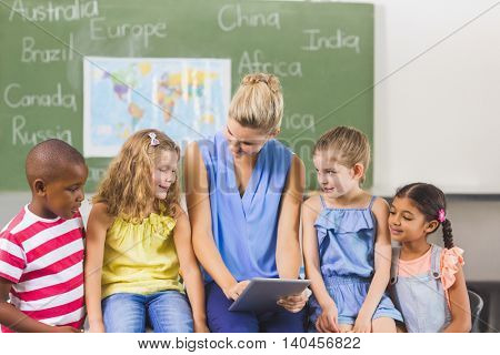 Teacher teaching kids on digital tablet in classroom at school
